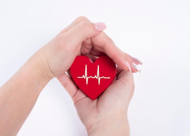 Mano della donna che tiene cuore rosso, battito cardiaco. concetto di salute