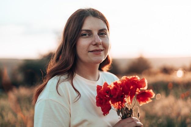 Mano della donna che tiene il mazzo dei papaveri rossi al tramonto nel campo