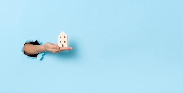 Mano della donna che tiene piccola casa attraverso il foro sullo sfondo della carta blu. assicurazione e vendita casa concetto.