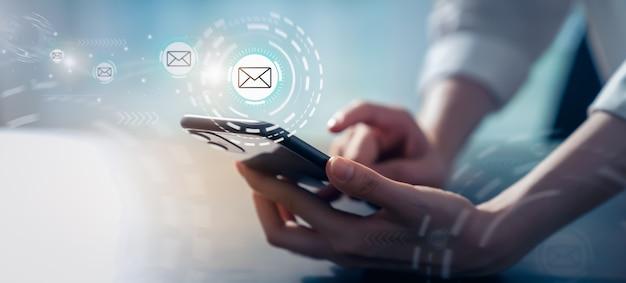 Mano della donna che tiene smartphone e mostra la schermata di posta elettronica sull'applicazione mobile in ufficio.