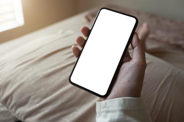 Smartphone della tenuta della mano della donna con il bokeh della sfuocatura. cellulare a schermo vuoto per montaggio display grafico