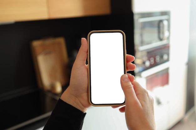 Mano della donna che tiene smartphone con schermo bianco verticale sulla cucina di casa