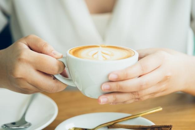 Mano di donna che tiene una tazza di caffè bianco