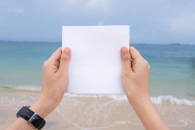 Mano della donna che tiene carta bianca con la spiaggia del mare e lo sfondo dell'onda morbida