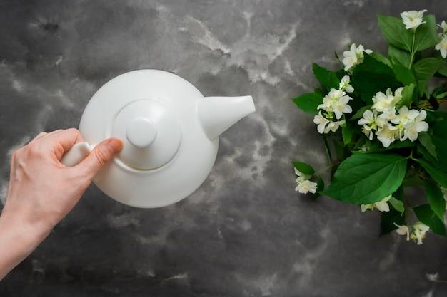 Mano della donna che tiene la disposizione piana del piano di marmo bianco nero del fiore del gelsomino della teiera bianca. insegna di web lungo del modello di vista superiore dell'ora del tè