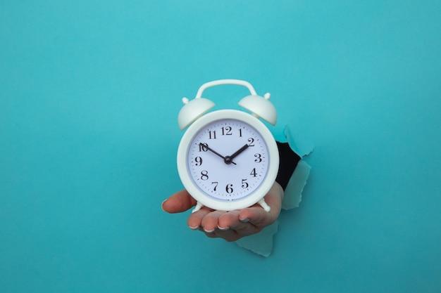La mano della donna tiene la sveglia attraverso un foro di carta blu. gestione del tempo e concetto di scadenza