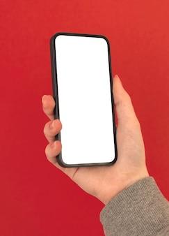 La mano della donna tiene il telefono cellulare moderno con lo schermo bianco vuoto su sfondo colorato psatel, copia spazio foto