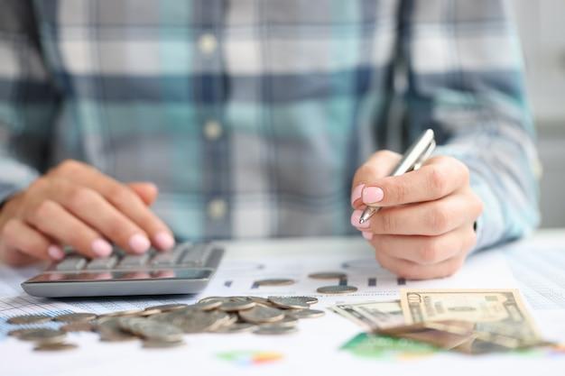 La mano della donna tiene la penna e considera le spese aziendali