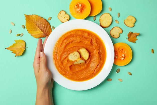 La mano della donna tiene il piatto di zuppa di zucca sulla menta
