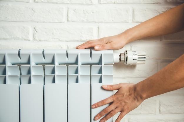 Mano della donna nel radiatore caldo sul fondo del muro di mattoni