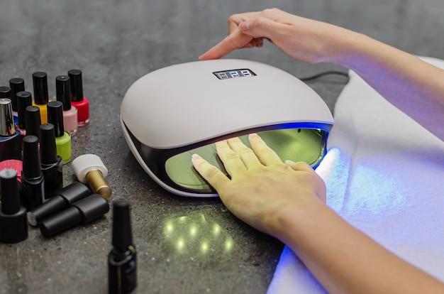 Mano della donna all'interno della lampada per unghie sul primo piano del tavolo. lampada uv per asciugare le unghie con il metodo del gel. unghie viola essiccate in una lampada.