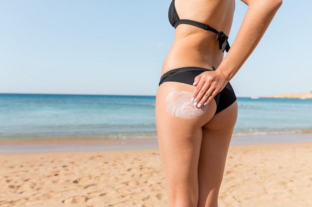 La mano della donna sta applicando la crema solare sui glutei in spiaggia sullo sfondo del mare.