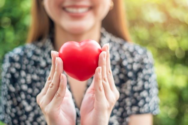 La mano della donna sta tenendo il cuore rosso