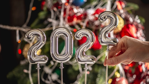 La mano della donna sta impostando l'ultimo simbolo 2 nel numero 2022 sullo sfondo di un bellissimo albero di natale festivo decorato. concetto del nuovo anno, saluto in vacanza.