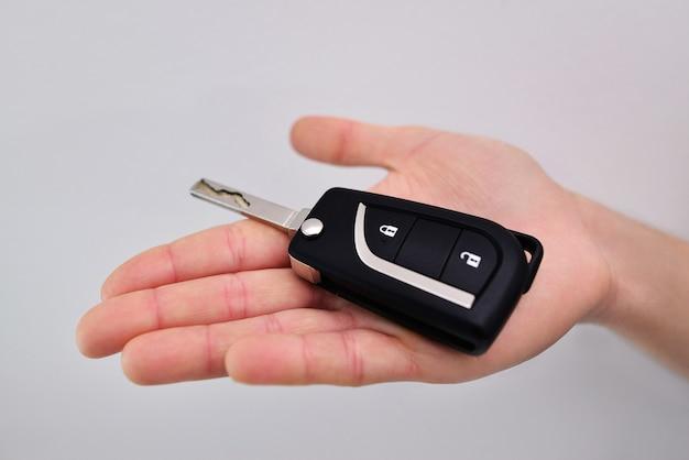 Mano della donna su priorità bassa isolata che tiene una chiave dell'automobile. venditore di auto. apertura e segnalazione