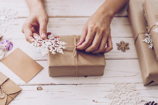 Mano della donna che fa bella scatola regalo di natale al tavolo