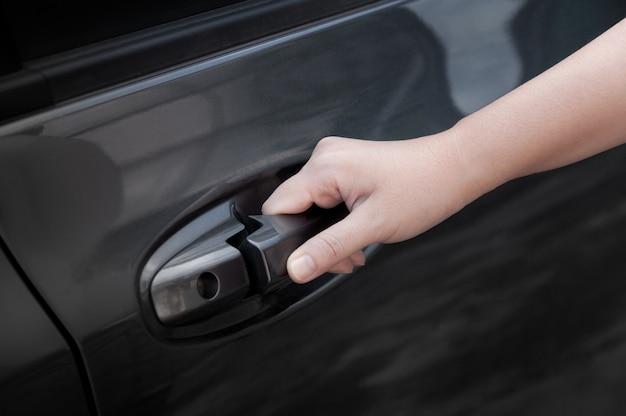 Porta della macchina aperta della mano della donna, mano che tira la maniglia della porta dell'auto