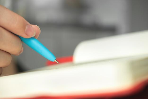 Mano e penna della donna con il primo piano del taccuino, scrittura di giovane artista, foto concettuale di hobby o lavoro di design
