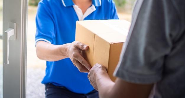 La mano della donna prende la scatola di consegna dal fattorino