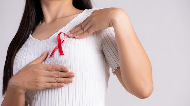 Mano della donna che indica il nastro rosso del distintivo sul petto per sostenere la giornata dell'aids. assistenza sanitaria .
