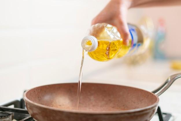 Una mano di donna versa olio da cucina sulla padella a casa
