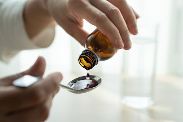 Mano della donna versando farmaci o sciroppo per la tosse dalla bottiglia al cucchiaio. concetto di assistenza sanitaria