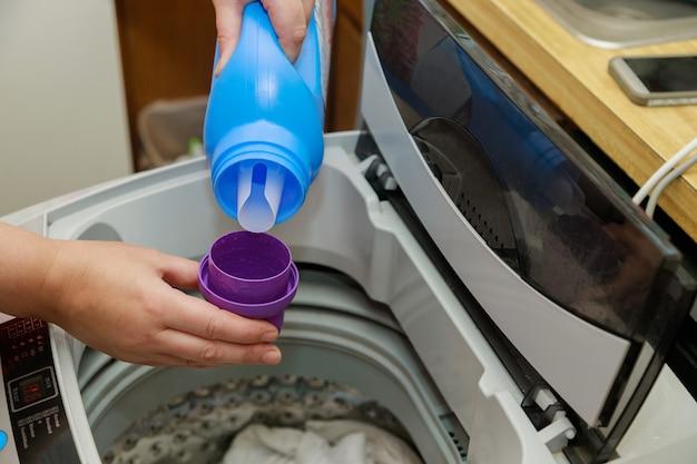 La mano della donna versa la polvere liquida nel tamburo del bucato della lavatrice