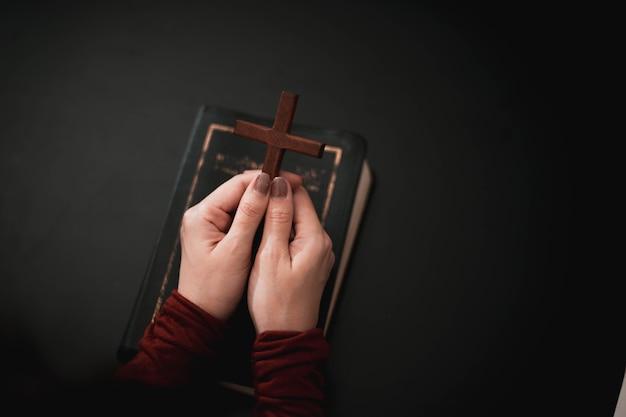 Mano della donna che prega sulla sacra bibbia al mattino.
