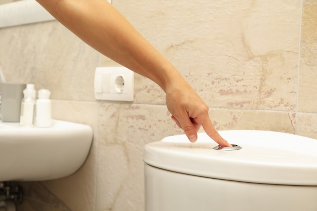 La mano della donna preme il pulsante dello sciacquone