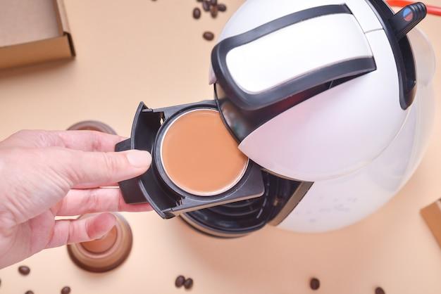 La mano della donna mette la capsula alla macchina del caffè