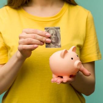 Mano della donna che mette 100 dollari nel porcellino per risparmiare ricchezza di denaro e concetto finanziario. - immagine