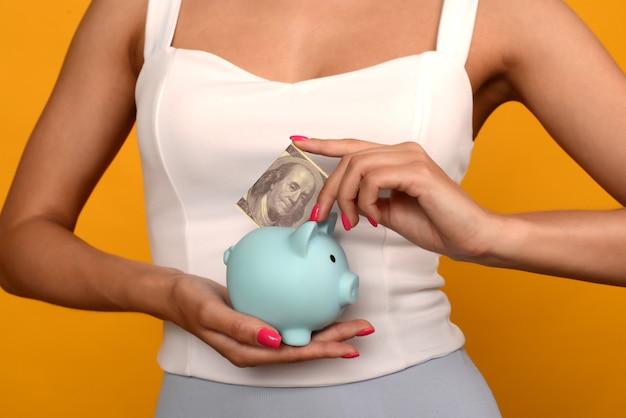 Mano della donna che mette i dollari nel salvadanaio per risparmiare ricchezza di denaro e concetto finanziario.