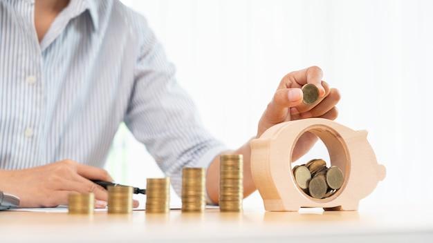 Mano della donna che mette la moneta dei soldi nel salvadanaio con il passo di monete crescenti dello stack per risparmiare denaro per il futuro concetto di investimento.