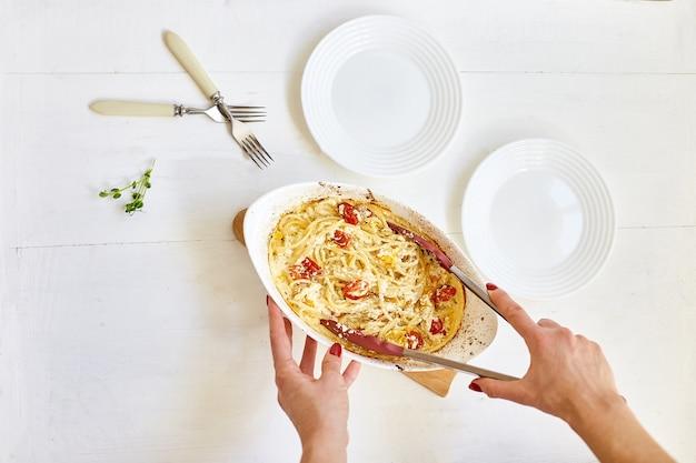 Mano della donna che cucina pomodori al forno virali e feta con pasta, fetapasta su una superficie di legno bianca. nuovo, popolare piatto per la cena, vista dall'alto, copia spazio.