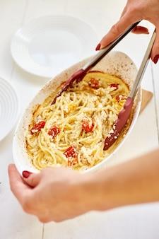 Pomodori al forno virali di tendenza di cottura della mano della donna e feta con la pasta