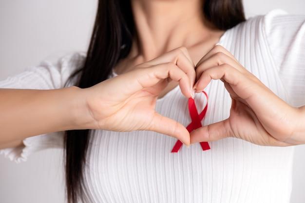 Mano della donna a forma di cuore con il nastro rosso distintivo sul petto per l'aids day.