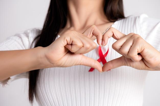 Mano della donna a forma di cuore con nastro distintivo rosso sul petto per sostenere la giornata dell'aids