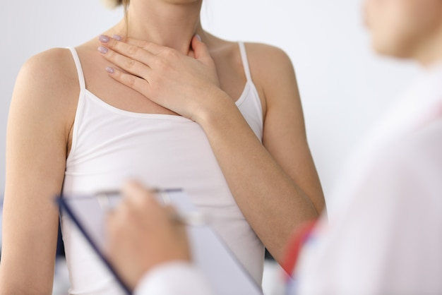 Mano della donna che mostra il collo irritato al primo piano di appuntamento del medico doctor