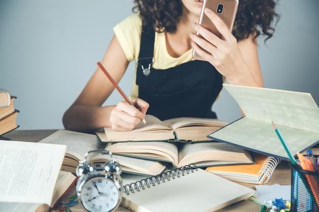 Telefono astuto della mano della donna con i libri sulla scrivania