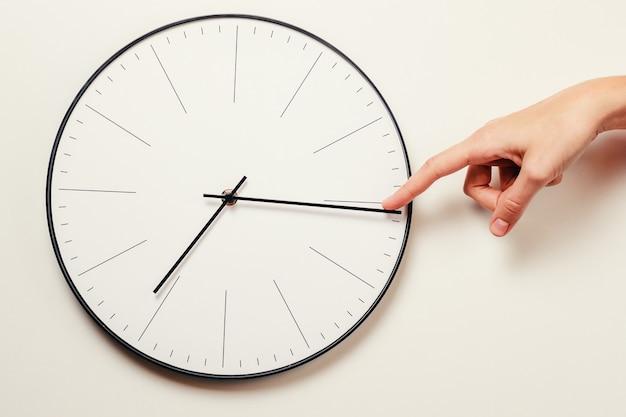 Tempo di arresto della mano della donna su un orologio rotondo, sulla gestione di tempo e sul concetto di scadenza