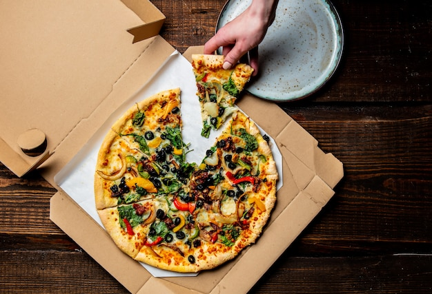 La mano della donna prende una pizza mediterranea con olive e formaggio da cartone in un piatto
