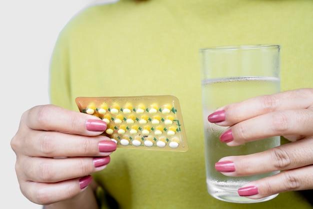 Mano della donna che prende il controllo delle nascite o le pillole contraccettive