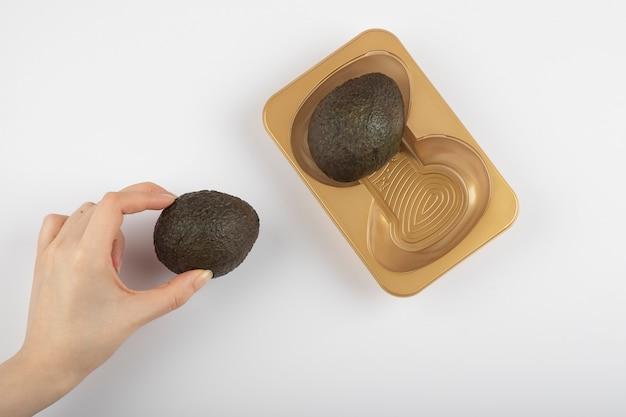Mano della donna che prende un avocado marrone isolato sul tavolo bianco-grigio.