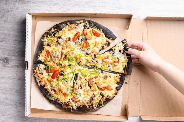 Mano della donna che cattura fetta di pizza deliziosa sul nero croccante dalla scatola, vista dall'alto