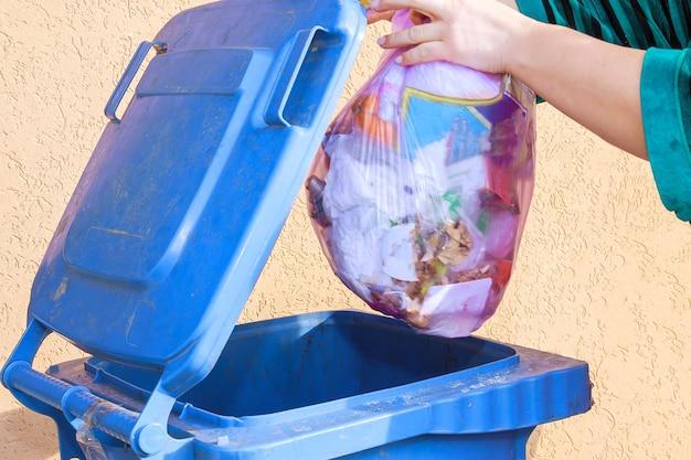 Mano della donna che getta immondizia nel contenitore della spazzatura.