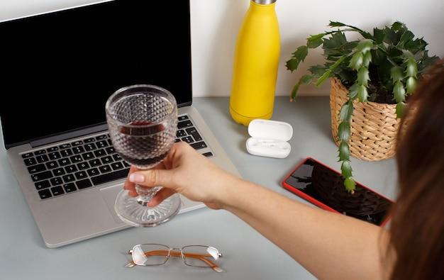 Brindisi della mano della donna con il computer portatile con un bicchiere di vino rosso. due amici che fanno una videochiamata su un laptop a casa, primi piani
