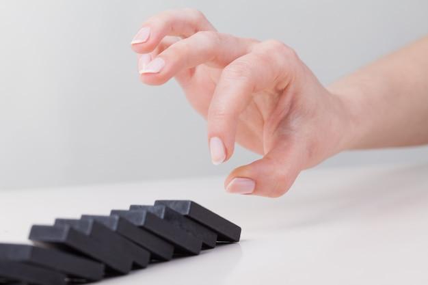 Mano di donna ribaltamento del domino. concetto di affari di reazione a catena foto premium