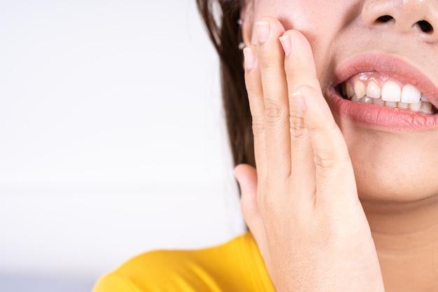 Mano della donna che tocca la sua guancia che soffre di mal di denti.