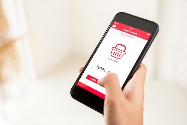 Schermo commovente dello smartphone della mano della donna, compera online digitalmente tramite l'applicazione