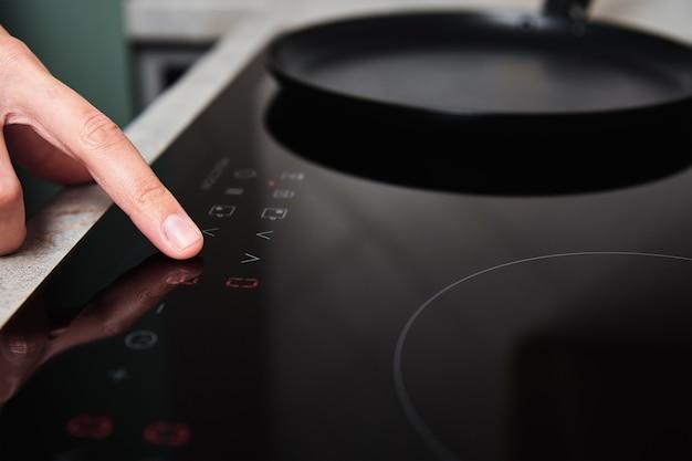 La mano della donna accende la moderna stufa a induzione in cucina